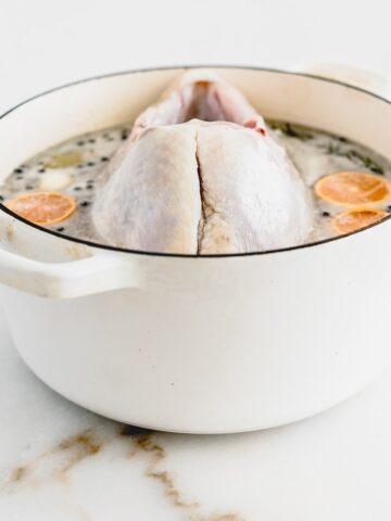 turkey breast brining in a white pot.