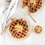 overhead view of 2 caramel apple waffles topped with apples on white plates with gold forks next to them.