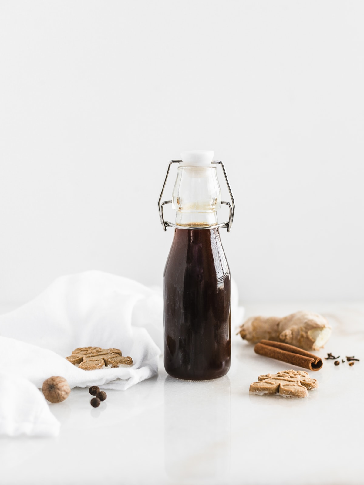 Gingerbread syrup in a glass container with cinnamon sticks and gingerbread cookies around it.