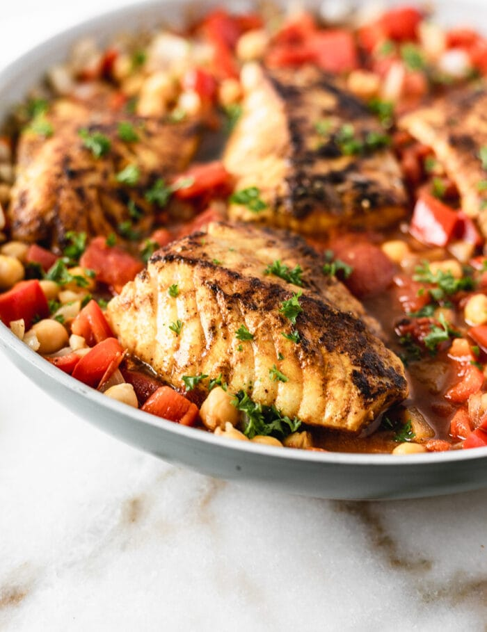 closeup of moroccan cod with stewed chickpeas and tomatoes in a skillet.