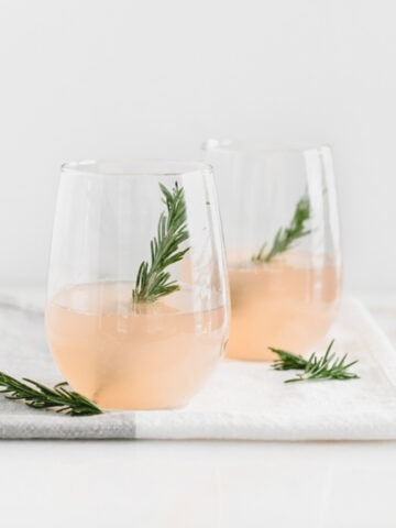two grapefruit prosecco cocktails garnished with rosemary in stemless wine glasses.