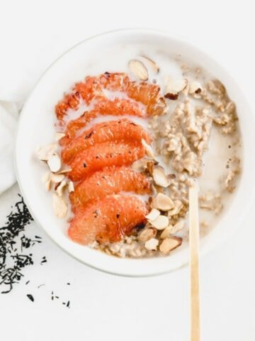 earl grey oatmeal with honey broiled grapefruit and toasted almonds on top in a bowl with a gold spoon.
