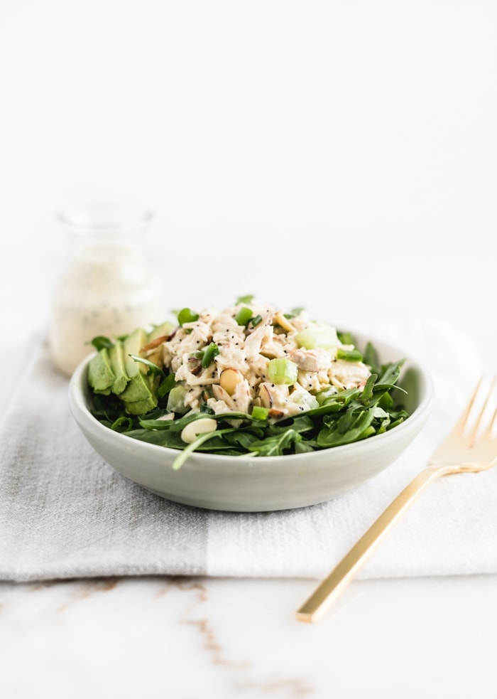 no mayo orange poppy seed chicken salad on greens in a bowl