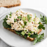 no mayo orange poppy seed chicken salad on a piece of bread with greens on a white plate.