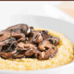 This creamy parmesan polenta with red wine mushrooms is a cozy, comforting vegetarian meal that will warm you from the inside! This simple, savory dish comes together in only 20 minutes thanks to quick cooking polenta. (#vegetarian, #nutfree, #glutenfree) #polenta #meatlessmeals #mushrooms #redwine #winter #comfortfood #healthy #recipes #maindish