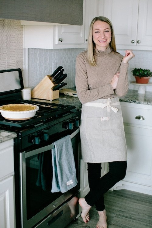 woman standing in kitchen wearing brown shirt, black pants and an apron with pie and kitchen knives in background