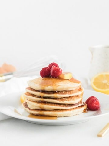 stack of healthy lemon ricotta pancakes with raspberries and syrup on top on a white plate.