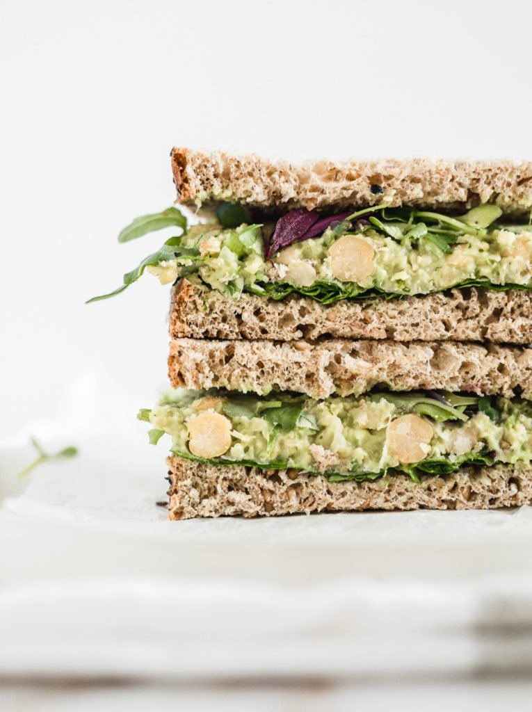 Close up picture of vegan chickpea avocado salad sandwich on a plate cut in half stacked on top of one another.