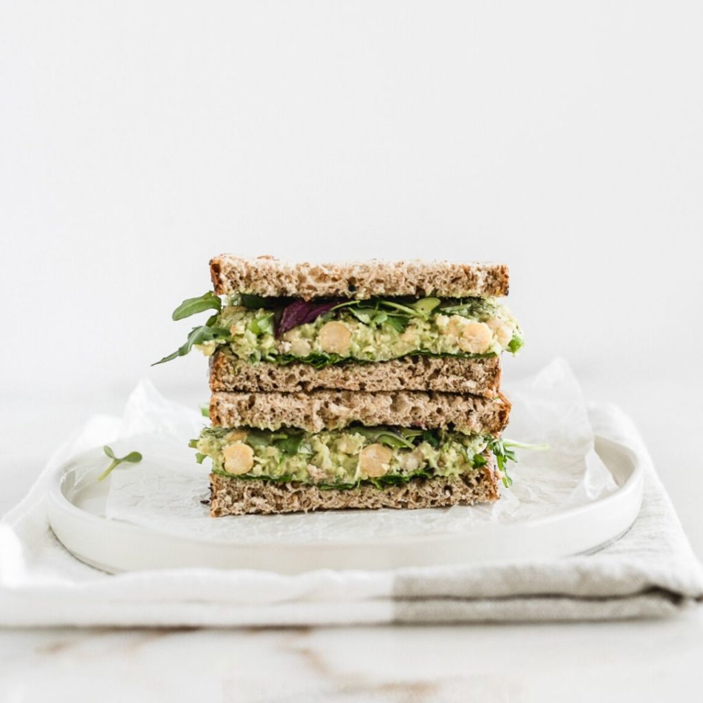 Close up of a smashed chickpea avocado salad sandwich cut in half stacked.