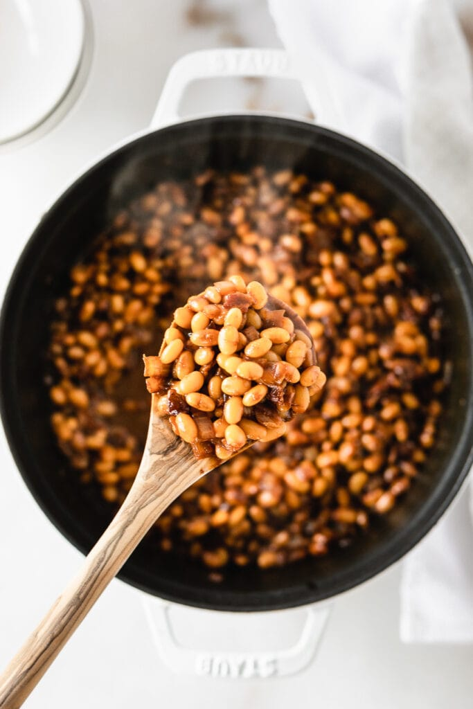 overhead view of a wooden spoon filled with baked beans over a pot of beans.