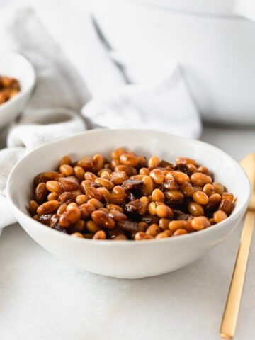 homemade baked beans in a white bowl with a gold spoon beside it.