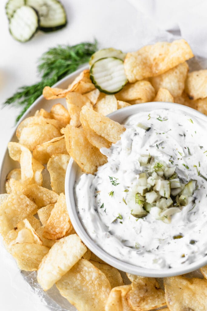 overhead view of a bowl of dill pickle dip surrounded by potato chips with 2 potato chips dipped into it.