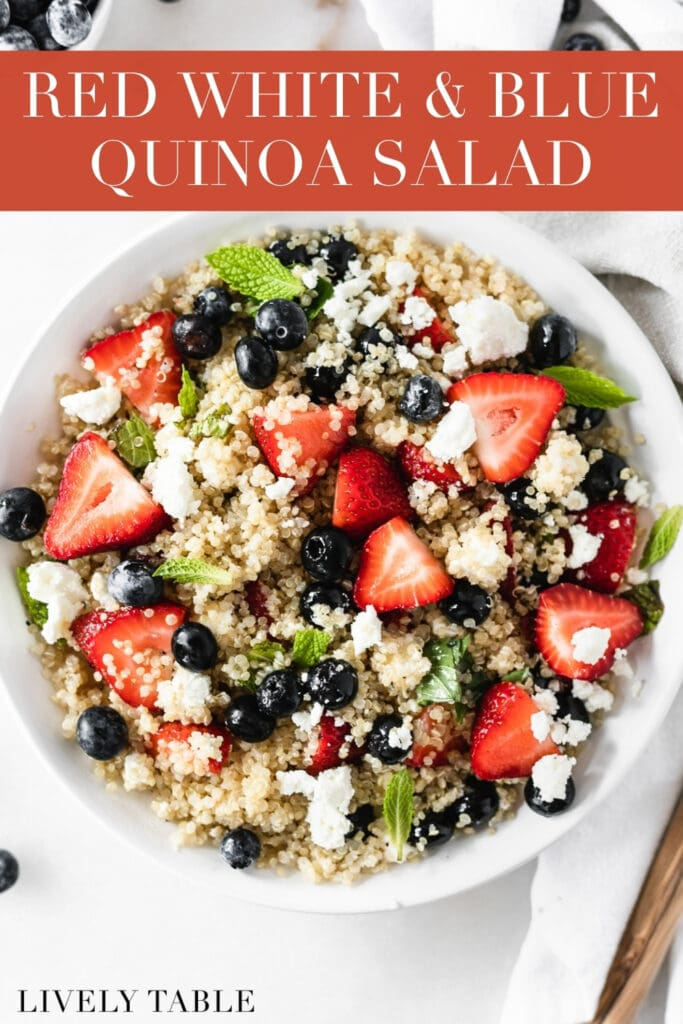 overhead view of red white and blue berry quinoa salad in a white bowl with text overlay.