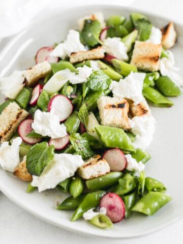 snap pea salad with burrata, min, sourdough croutons, and lemon vinaigrette on a white plate.