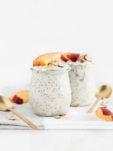 peach overnight oats in 2 glass jars with spoons beside them on a white and grey napkin.