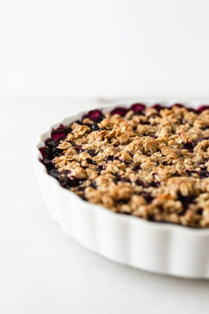 closeup of a blueberry peach crumble in a round white baking dish.