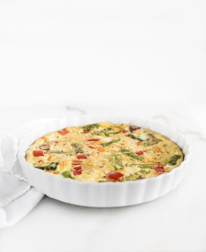 veggie frittata in a white round baking dish.