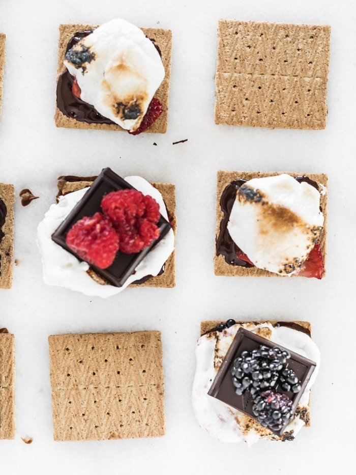 overhead view of 6 graham crackers topped with chocolate, berries and toasted marshmallows