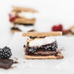 a dark chocolate berry s'more with melted chocolate and blackberries with stacked s'mores in the background