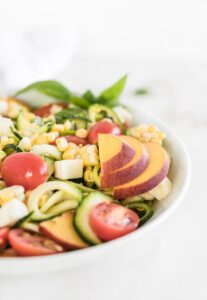 closeup of corn, zucchini noodles, tomato and mozzarella salad with sliced peach and basil on top in a white bowl