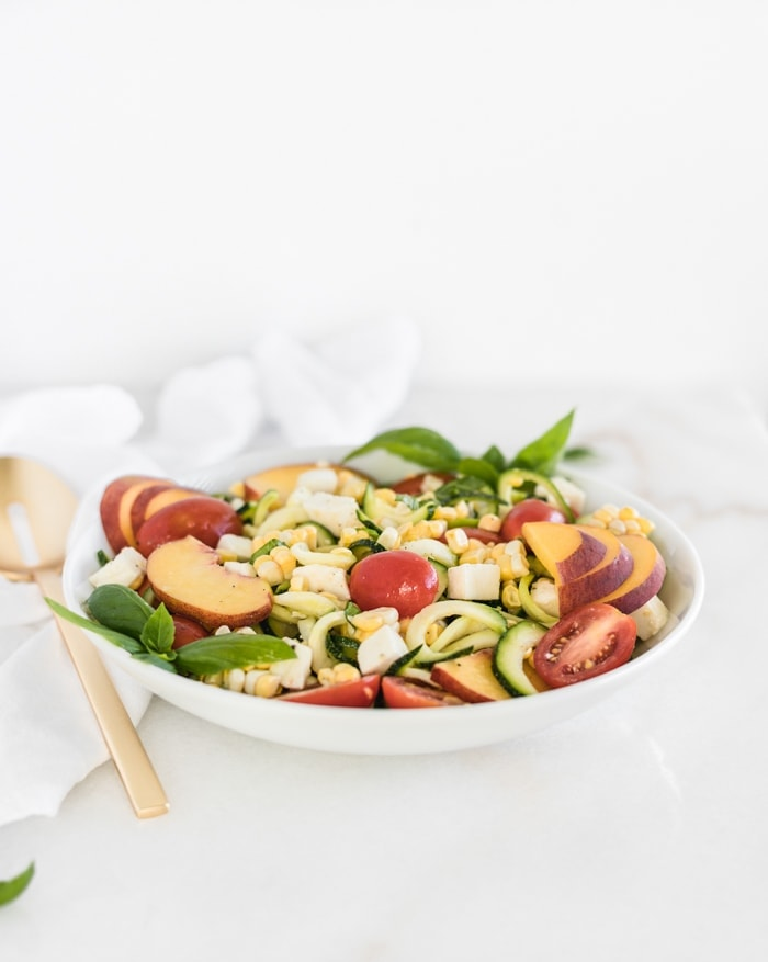 Summer caprese salad with zucchini noodles, corn, tomatoes, and peaches in a white bowl with a gold spoon next to it