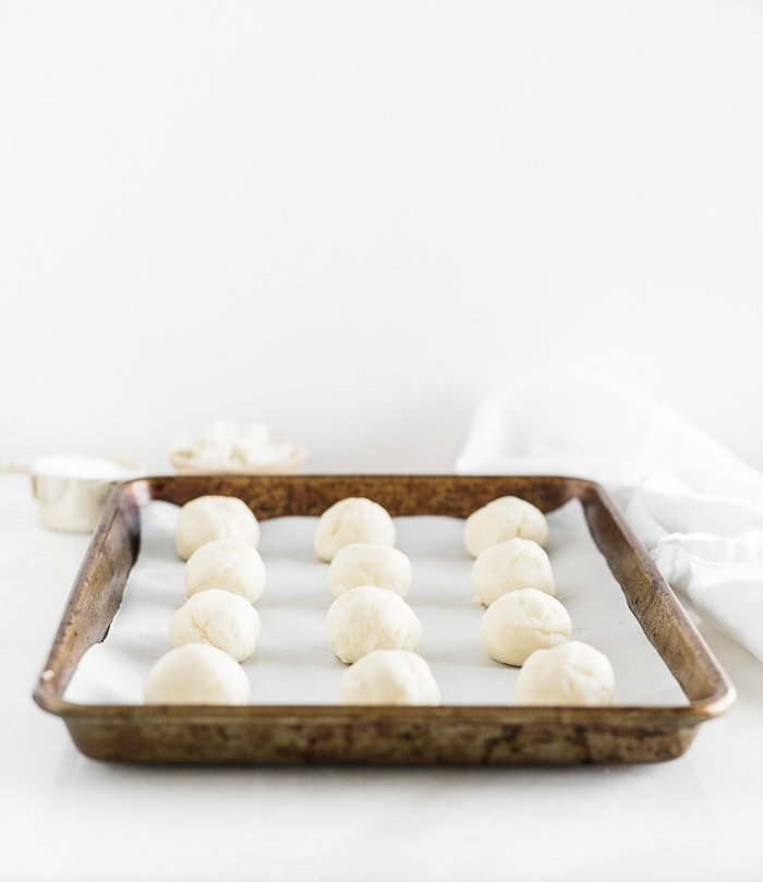 unbaked balls of cheese roll dough on a baking sheet