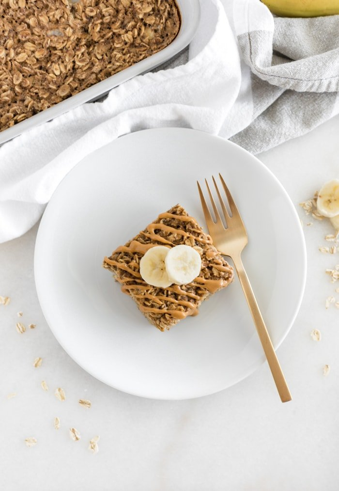 overhead shot of a square of peanut butter banana baked oatmeal drizzled with peanut butter and topped with banana slices on a white plate with a gold fork.