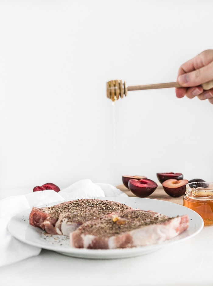 hand drizzling honey with a honey dipper over pork chops on a white plate with plums in the background.