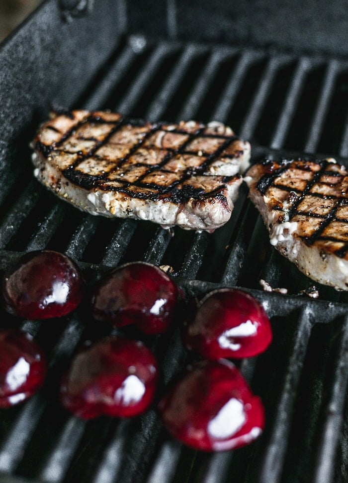 pork chops and halved plums on the grill.