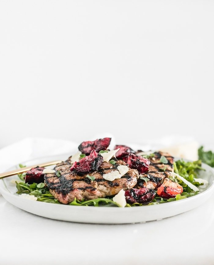 grilled pork chops on top of arugula with grilled plums and parmesan on top, on a white plate.