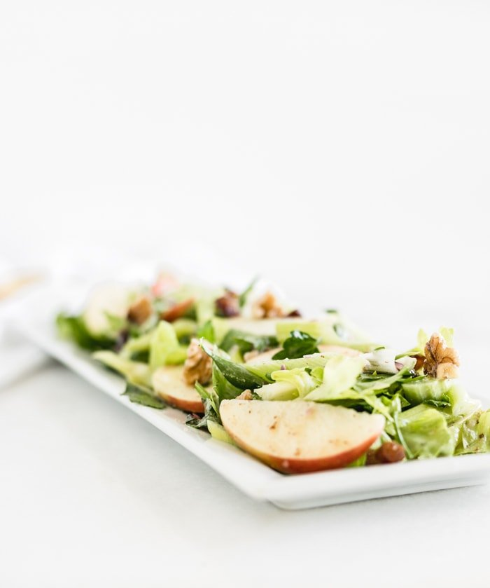 celery apple salad on a white rectangle serving dish.