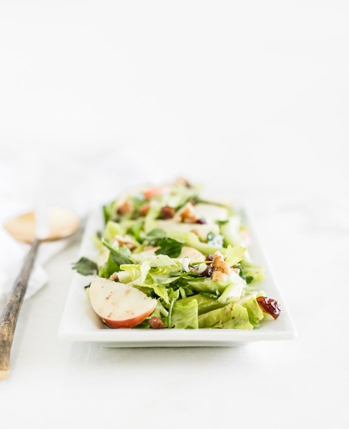 celery apple salad on a white rectangle platter.