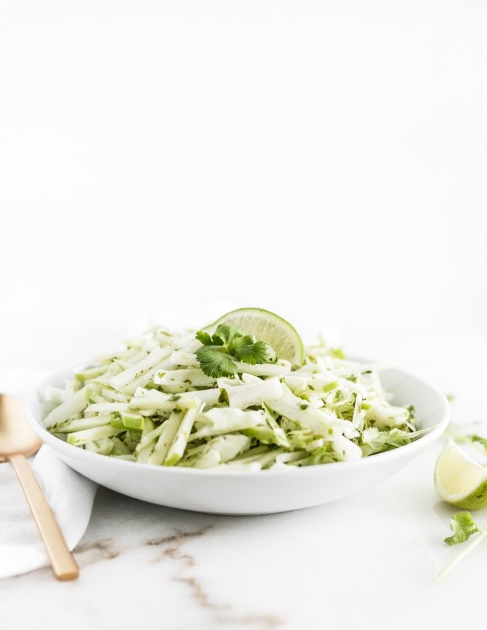green apple jicama slaw with a lime wedge on top in a white bowl
