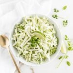 overhead shot of green apple jicama slaw with a lime wedge on top in a white bowl.