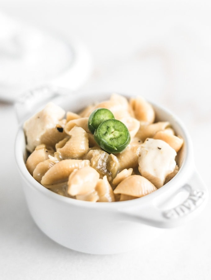 green chile chicken mac and cheese shells in a small white ramekin with jalapeno slices on top