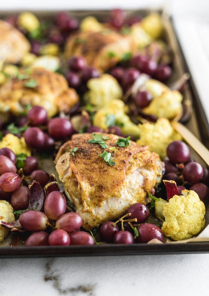 honey turmeric chicken thighs with cauliflower and grapes on a sheet pan.