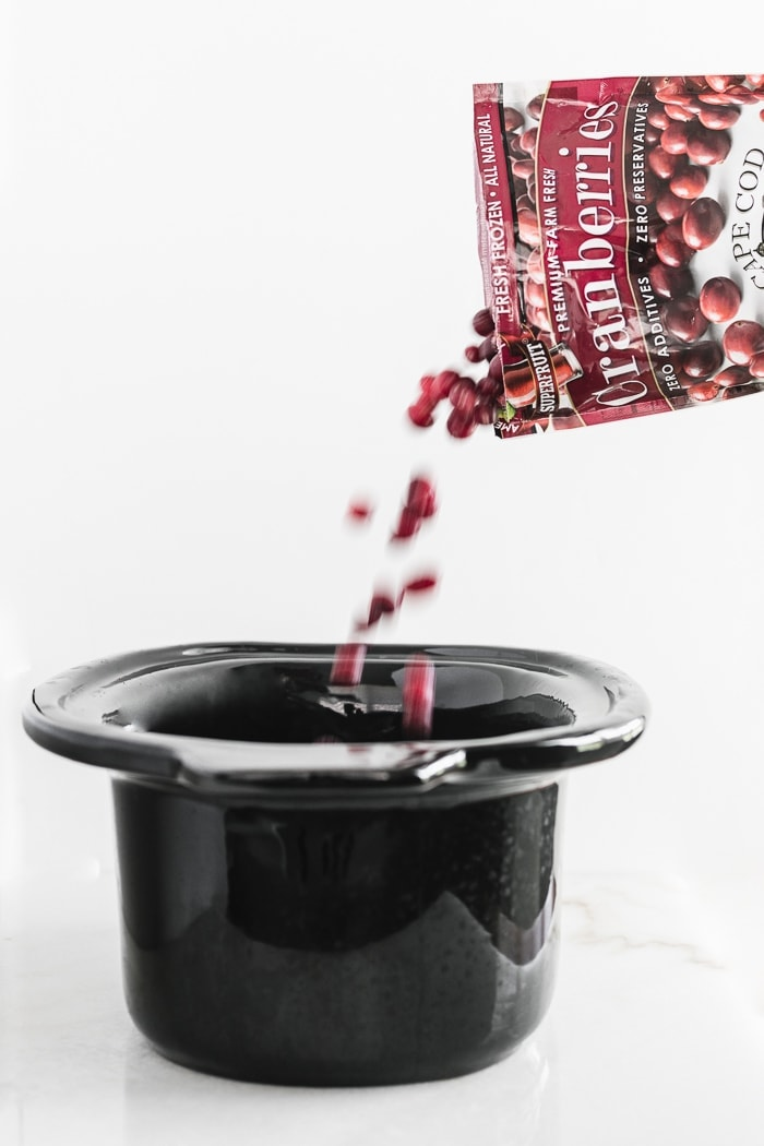cranberries being poured into the pot of a slow cooker.