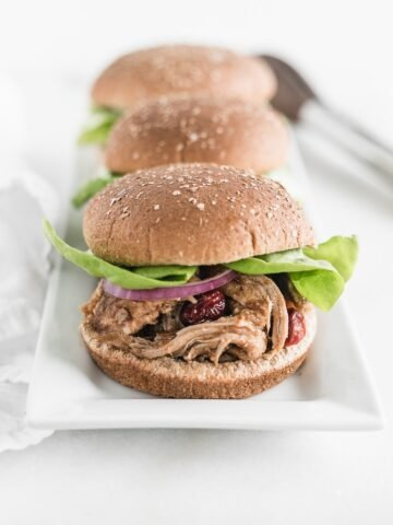 cranberry chipotle pulled pork sandwiches on bun with lettuce lined up on a white platter.