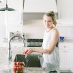 Woman in a blue tank top washing strawberries at the kitchen sink.