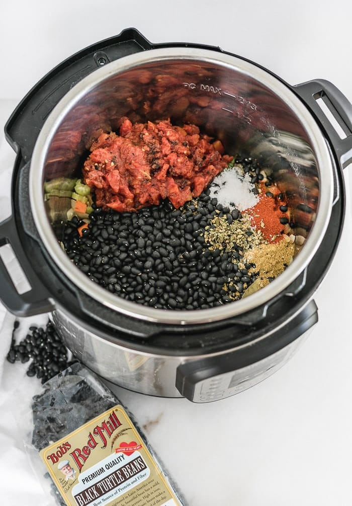 beans, canned tomatoes, and spices in an instant pot, with a bag of black beans beside it.