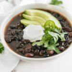mexican black bean soup in a white bowl, topped with sour cream, avocado and cilantro.
