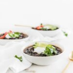 three white bowls of mexican black bean soup.