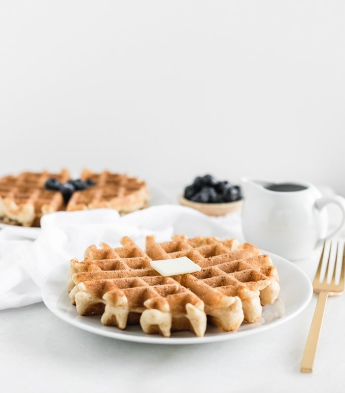 whole wheat waffle with a pat of butter on a white plate and a gold fork beside it with syrup, blueberries and another waffle in the background.