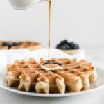 syrup being poured onto a whole wheat waffle on a white plate with blueberries and a waffle in the background.