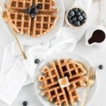 overhead view of thwo whole wheat buttermilk waffles on white plates with gold forks, a dish of syrup, and a bowl of blueberries.
