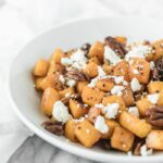 closeup of roasted butternut squash with goat cheese and pecans in a white bowl.