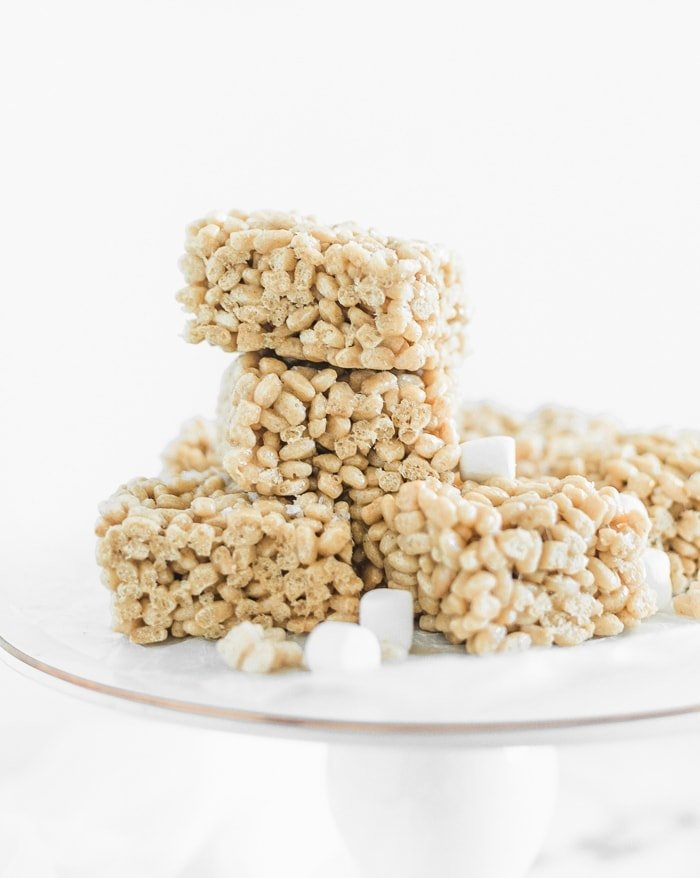 brown brutter bourbon rice krispie treats stacked on a white serving stand surrounded by mini marshamllows.