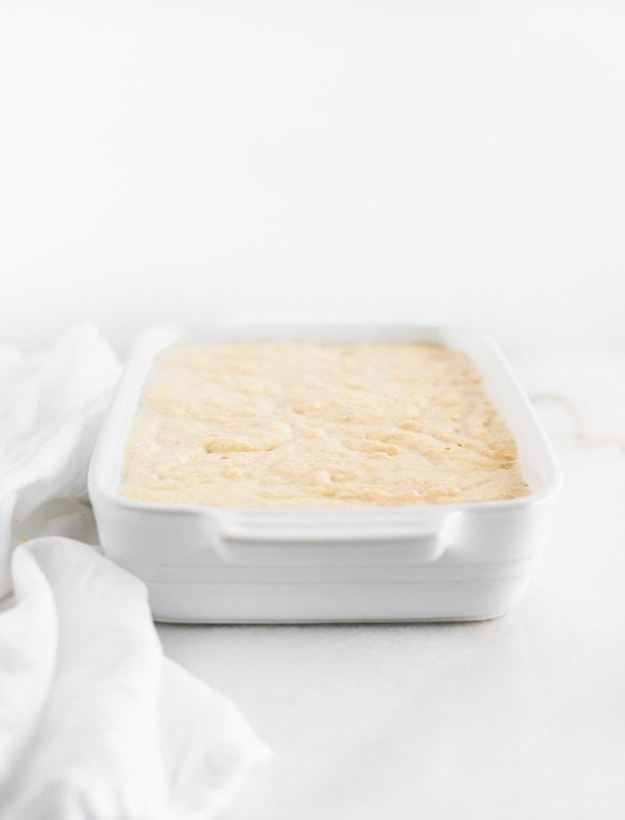 cornbread batter spread in a white rectangular baking dish.