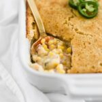southwest creamed corn casserole with cornbread topping in a white rectangular baking dish with a gold spoon in it.