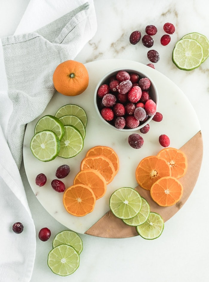 sliced limes and oranges and a bowl of frozen cranberries on a white and copper serving platter.